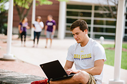 Photo of a student working on his laptop while sitting outside. Link to Closely Held Business Stock.